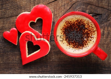 Happy Valentine's day or Good morning concept - a red cup of frothy coffee with sugar icing decorated heart shaped romantic cookies - stock photo