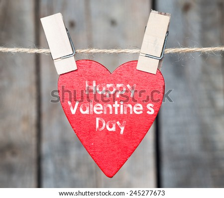 Happy Valentines day. Happy Valentines day and heart hanging on a rope - stock photo