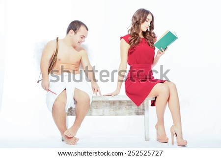 Happy Valentines day. Portrait of an adorable little cupid sitting on the bench with a beautiful woman reading a book isolated on white with copy space - stock photo