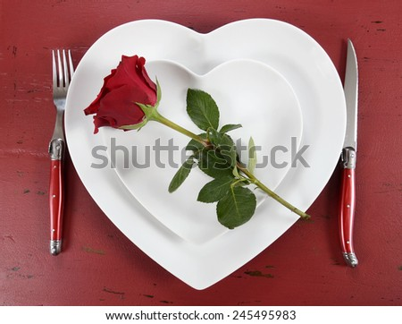 Happy Valentines Day table place setting on red vintage wood background with red rose, overhead. - stock photo
