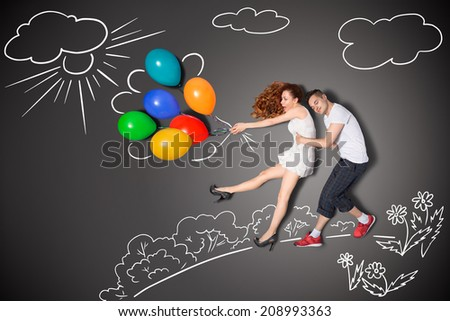 Happy valentines love story concept of a romantic couple holding balloons blowing with the wind against chalk drawings background. - stock photo
