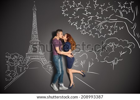 Happy valentines love story concept of a romantic couple in Paris kissing under the Eiffel Tower against chalk drawings background. - stock photo