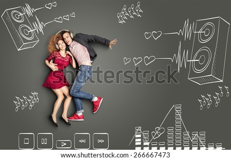 Happy valentines love story concept of a romantic couple sharing headphones and listening to the music against chalk drawings background of acoustic system, equalizer and player icons. - stock photo