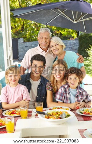 Happy vegetarian family eating healthy with salad at lunch - stock photo