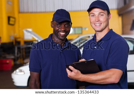happy vehicle service center manager and worker inside workshop - stock photo
