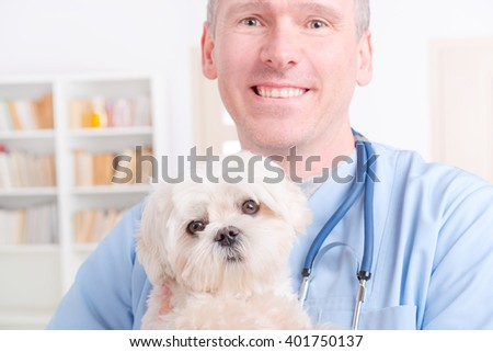 Happy vet with little dog maltese and stethoscope - stock photo