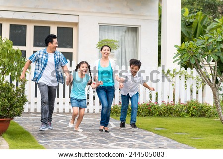 Happy Vietnamese family running together in the backyard - stock photo