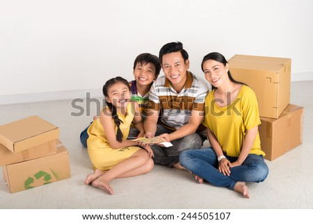 Happy Vietnamese family sitting on the floor with moving boxes and color samples - stock photo