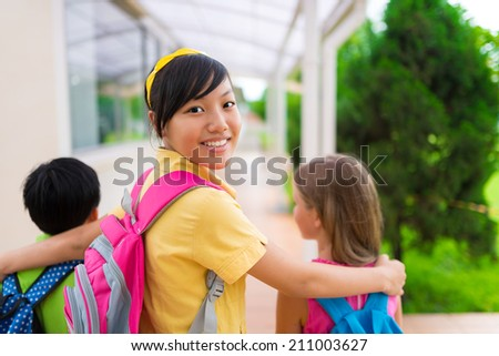 Happy Vietnamese girl hugging her classmates and looking at camera on her way to school - stock photo