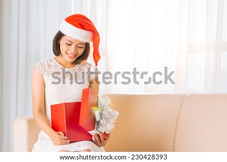 Happy Vietnamese woman opening Christmas gift - stock photo