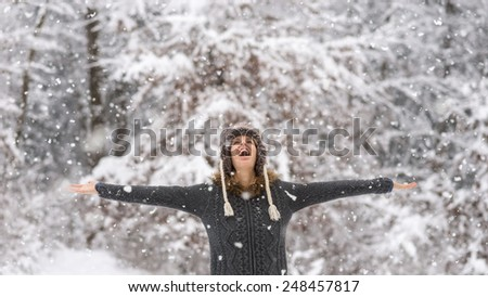 Happy vivacious woman celebrating the winter snow standing with her arms outspread in a snowy forest laughing as she watches the falling snowflakes from above. - stock photo