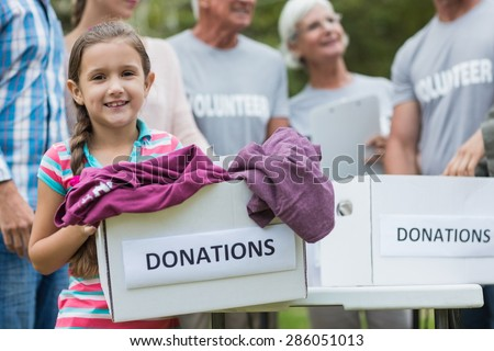 Happy volunteer family holding donation boxes on a sunny day - stock photo