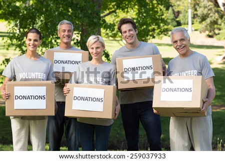 Happy volunteer family holding donations boxes on a sunny day - stock photo