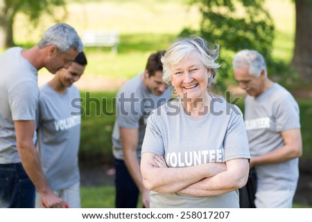 Happy volunteer grandmother smiling at camera on a sunny day - stock photo