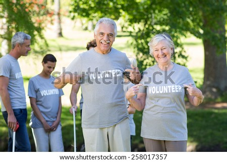 Happy volunteer senior couple smiling at the camera on a sunny day - stock photo