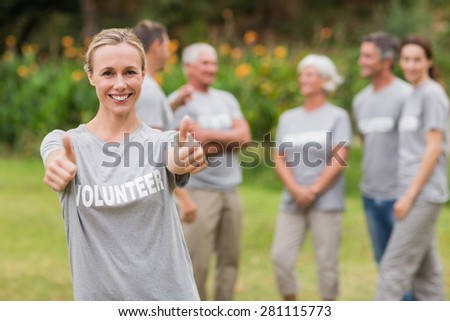 Happy volunteer with thumb up on a sunny day - stock photo