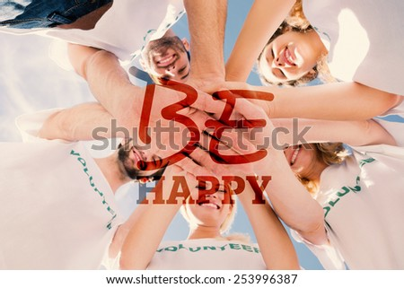 Happy volunteers with hands together against blue sky against be happy - stock photo