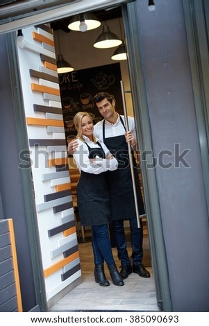 Happy waiter and waitress standing at entrance of cafeteria, smiling, looking at camera. - stock photo