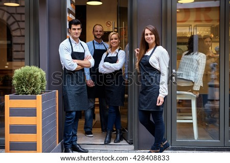 Happy waiters and waitresses standing at the entrance of cafeteria, smiling, looking at camera, wearing apron. - stock photo