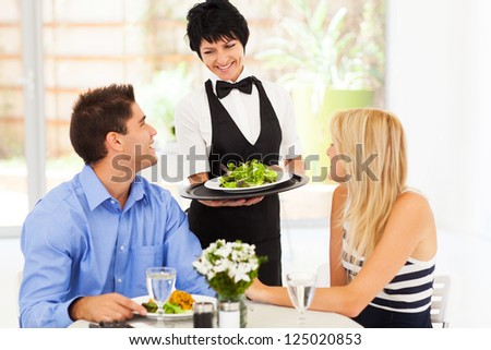happy waitress serving customers in restaurant - stock photo