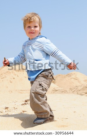 happy walking  kid on the sea beach against blue sky - stock photo