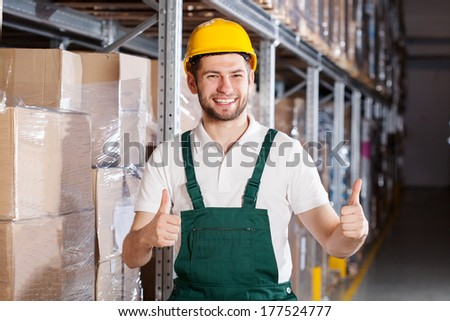 Happy warehouse worker in yellow hardhat showing ok sign - stock photo