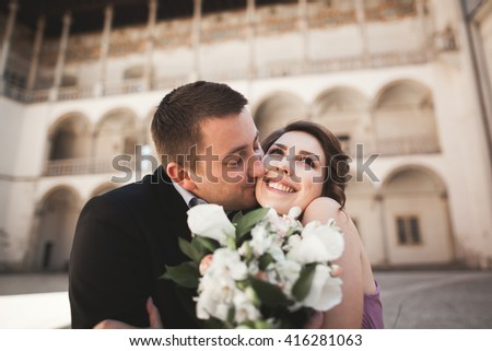 Happy wedding couple, groom, bride with pink dress hugging and smiling each other on the background walls in castle - stock photo