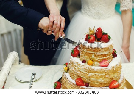 Happy wedding couple handsome groom and blonde bride carving delicious wedding cake - stock photo