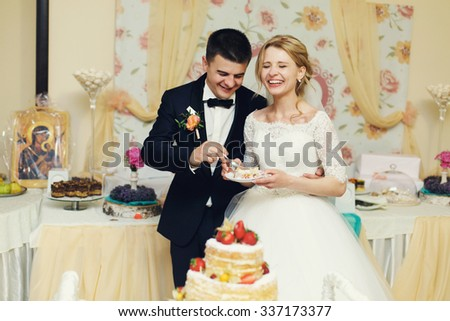 Happy wedding couple handsome groom and blonde bride eating delicious wedding cake - stock photo
