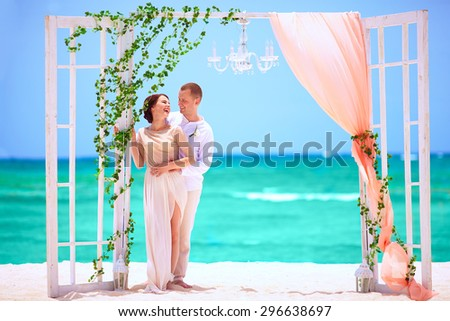 happy wedding couple on decorated tropical beach - stock photo
