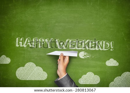 Happy weekend concept on green blackboard with businessman hand holding paper plane - stock photo