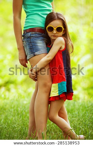 Happy weekend concept. Portrait of fashionable gorgeous baby girl in trendy sunglasses hugging her mother. Family walking in the park. Stylish casual clothes. Sunny summer day. Outdoor shot - stock photo