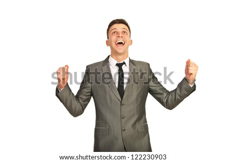 Happy winner business man looking up and cheering isolated on white background - stock photo