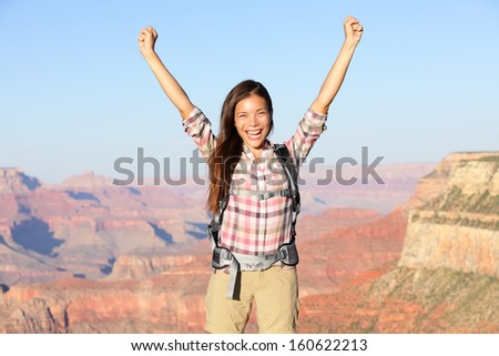Happy winner hiker in Grand Canyon cheering with arms raised up in winning gesture enjoying the beautiful landscape. Hiking girl wearing backpack during summer in Grand Canyon, Arizona, United States. - stock photo