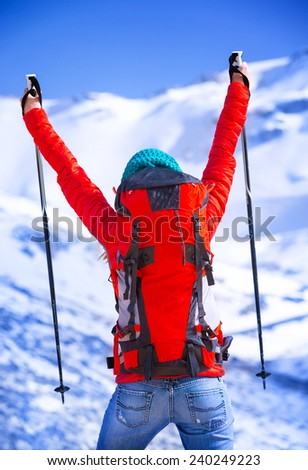 Happy winner of winter sport games, back side of cheerful skier with raised up hands enjoying competition, wintertime activities - stock photo