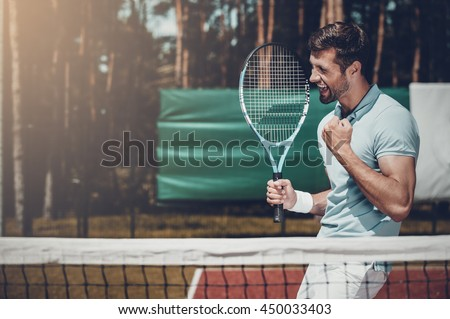 Happy winner. Side view of happy young man in polo shirt holding tennis racket and gesturing while standing on tennis court - stock photo