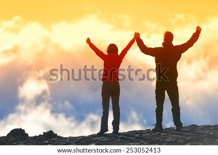 Happy winners reaching life goal - success people at summit. Business achievement concept. Two person couple together arms up in the air of happiness with accomplishment in the clouds at sunset. - stock photo