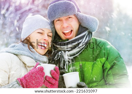 Happy Winter Couple Having Fun Outdoors. Snow. Winter Vacation. Hot Drink Outdoor. Joyful family  - stock photo