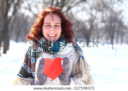 Happy winter girl with the red heart outdoors - stock photo