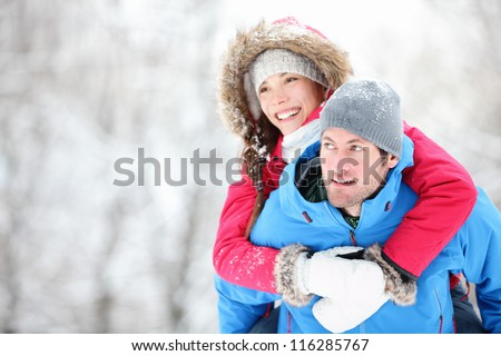 Happy winter travel couple. Man giving woman piggyback ride on winter vacation in snowy forest. Young interracial couple, Asian woman, Caucasian man. - stock photo