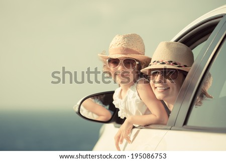 Happy woman and child in car against sea and sky background. Summer vacation concept. Toned image - stock photo