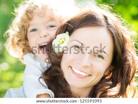 Happy woman and child in spring park - stock photo