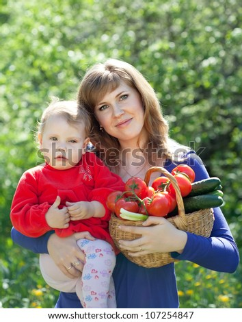Happy woman and child with  harvested vegetables in garden - stock photo