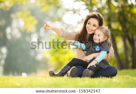 Happy woman and daughter showing to something in the park - stock photo