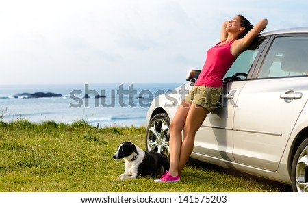 Happy woman and dog enjoying travel and peace on summer. Beautiful girl and her pet on road trip to coast. Copy space. - stock photo