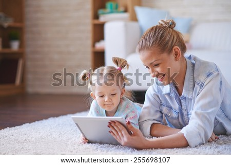 Happy woman and her daughter with digital tablet relaxing at home - stock photo