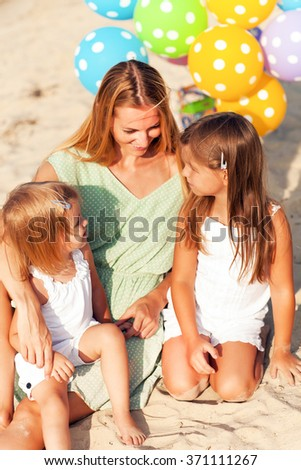Happy woman and her little daughters at the beach with ballons. Mother day or birthday concept - stock photo