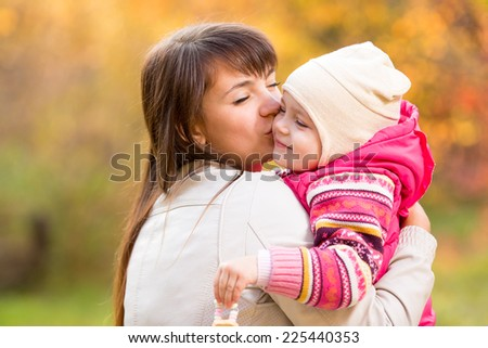 Happy woman and kid in golden autumn background. Mom kissing daughter. Mothers day holiday concept - stock photo