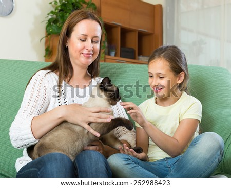 Happy woman and little smiling daughter sitting with cat at home - stock photo