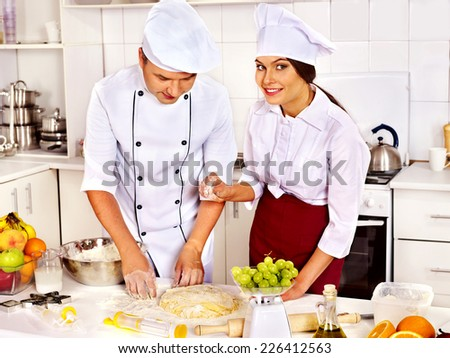 Happy woman and man in chef hat cooking dough . - stock photo